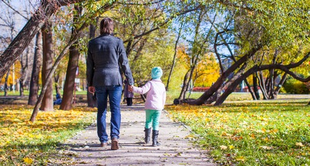 september 2: Young father and little girl walking in autumn park
