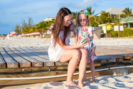 Happy mother and little daughter at caribbean beach photo