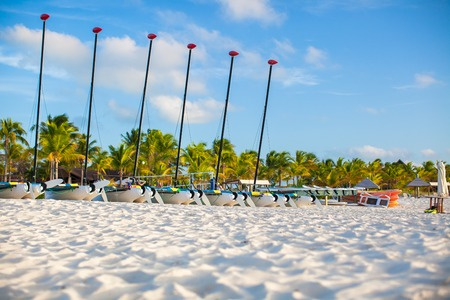 Group of catamarans with colorful sails on exotic Caribbean beach photo