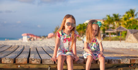 Two happy little girls enjoy vacation on white beach Stock Photo - 30817427
