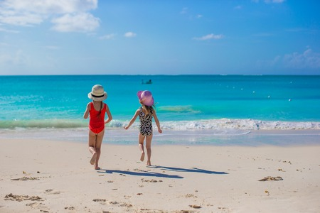 Two happy little girls enjoy vacation on white beach Stock Photo - 30817483