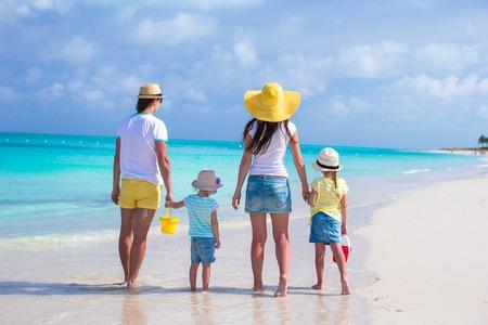 Happy family of four on caribbean holiday vacation photo