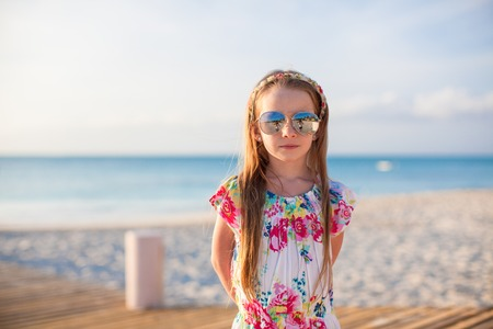 Adorable little girl walking at white tropical beach photo
