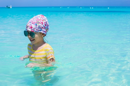 Happy little girl have fun at the sea during summer vacation photo