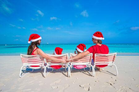 5 10 year old girl: Family in santa hats having fun on tropical beach