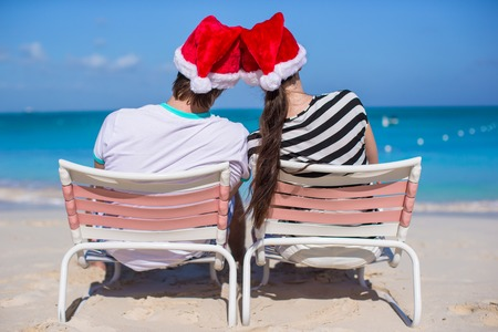 Young couple in Santa hats enjoy beach vacation photo