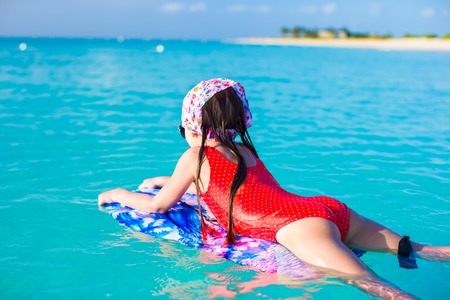 Little cute girl swimming on a surfboard in the turquoise sea