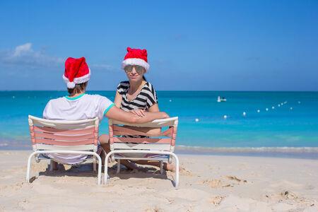 Back view of couple in Santa hats enjoy beach vacation photo