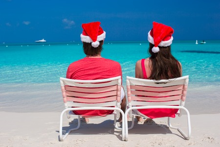 Happy romantic couple in red Santa Hats at tropical beach photo