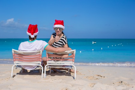 Young couple in Santa hats during beach vacation photo