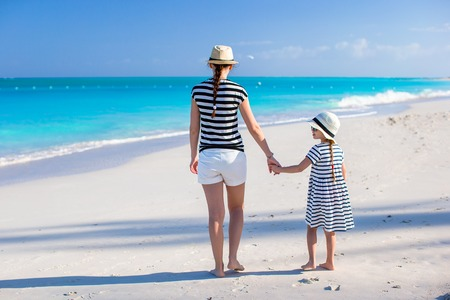 Back view of mother and little daughter at caribbean beach photo