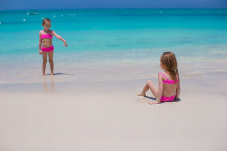 youngbaby: Little cute girls walking on white beach during vacation Stock Photo