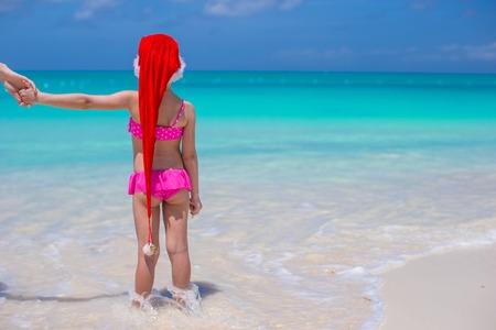 Little cute girl in red Santa hat on tropical beach photo