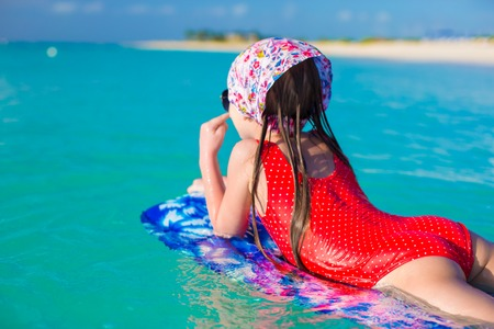 Little adorable girl on a surfboard in the turquoise sea photo