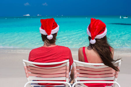 Happy young couple in red Santa Hats sitting on beach chairs photo