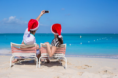 Young happy couple in red Santa hats taking a photo on cell phone photo