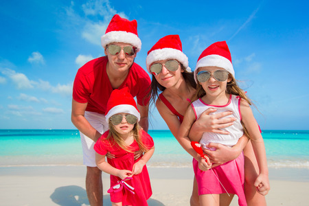 Portrait of happy family in Santa hats on the beach photo