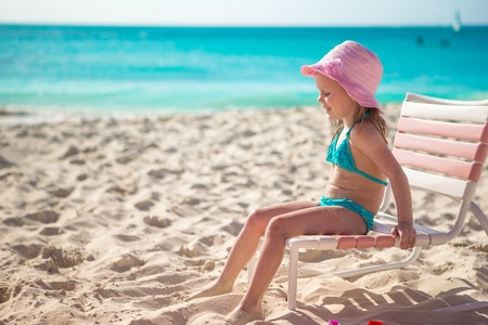 Adorable little girl in hat at beach during caribbean vacation photo