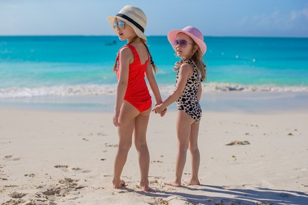 Two happy little girls enjoy vacation on white beach Stock Photo - 30817868