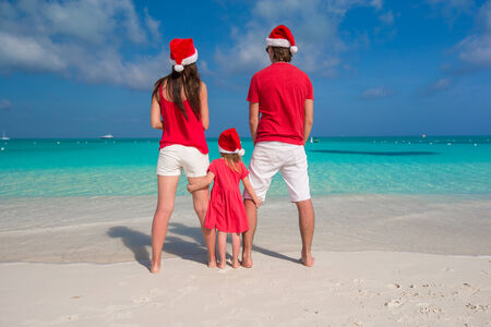 Happy family in Santa Hats having fun during caribbean vacation photo
