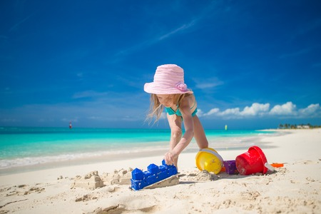 Little girl playing with beach toys during tropical vacation photo