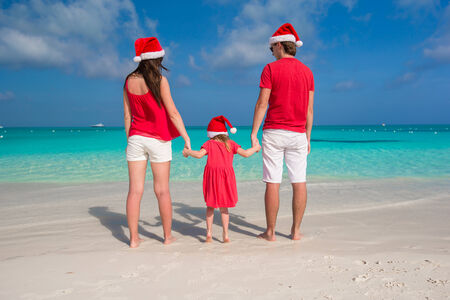 Happy family in Santa Hats having fun on white beach photo