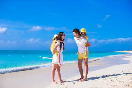 Happy family of four on caribbean holiday vacation photo