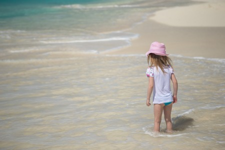 Adorable little girl playing in shallow water at perfect beach photo