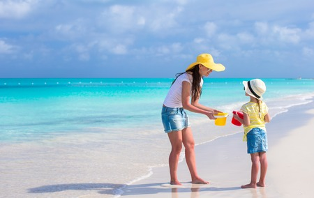 Mom and girl at tropical beach during summer vacation photo