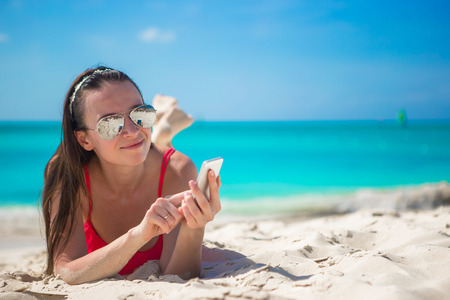 Young woman lying on white sand and talking on her phone photo