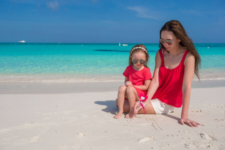Young beautiful mother and her adorable little daughter have fun at tropical beach photo