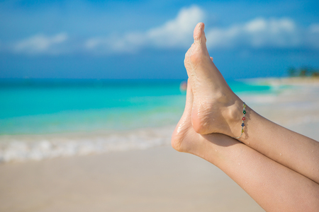 footsie: Close up of female feet on white sand beach