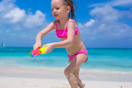 Cute little girl in hat at beach during summer vacation photo