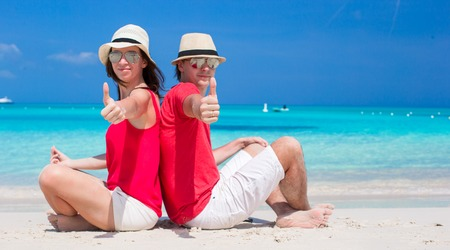 Close up of couple sitting in the heart on tropical beach photo