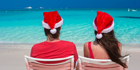 Happy romantic couple in red Santa hats at tropical beach relaxing on sunbeds photo