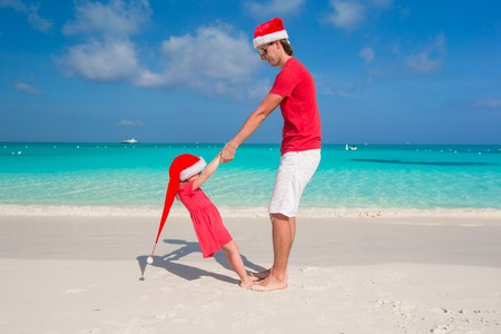 Young father and adorable little daughter in Christmas Hat photo