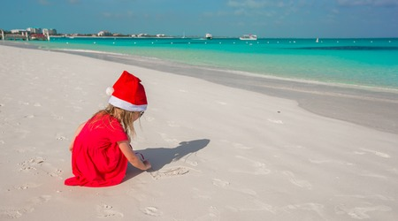 Little cute girl in red hat santa claus on the beach photo