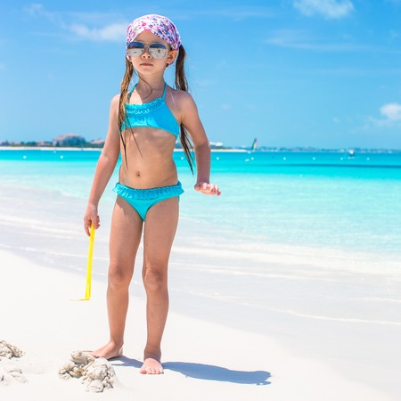 Cute little girl at beach during summer vacation photo
