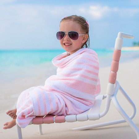 beach towel: Adorable little girl in sunglasses covered with towel Stock Photo