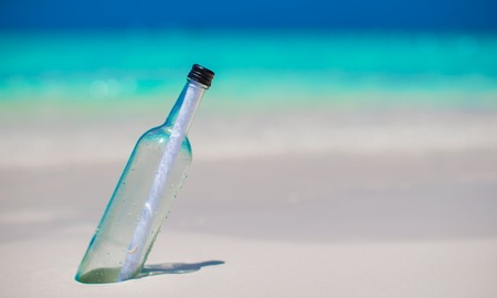 castaway: Bottle with a message buried in the sand Stock Photo