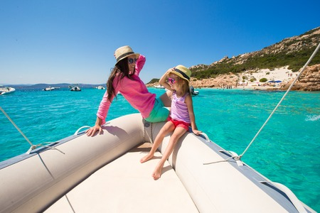 Young mother with her adorable daughter enjoy vacation on a boat photo