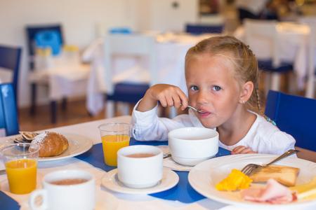 outdoor restaurant: Adorable little girl having breakfast at restaurant