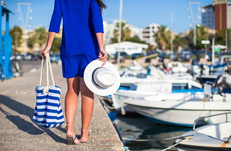Young beautiful woman walking with hat and bag on dock near the boat photo