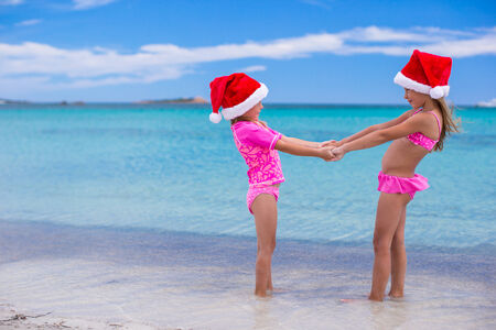 Little cute girls in Christmas hats having fun on exotic beach photo