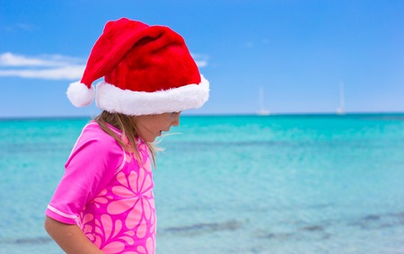 Little adorable girl wearing Santa hat at tropical beach photo