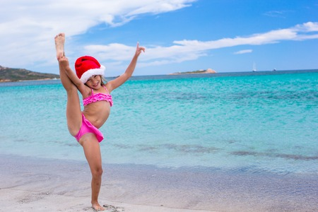 Smiling little girl making stretching exercise in Santa Hat on white beach photo