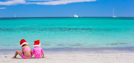 Little adorable girls in Santa hats during their beach tropical vacation photo