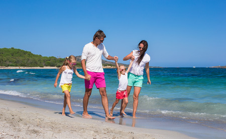Happy family of four on beach vacation photo