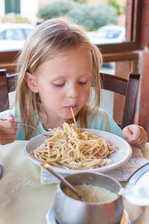 playing with spoon: Adorable little girl eating spaghetti in outdoors restaraunt