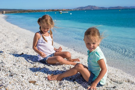 Adorable cute girls have fun on white beach during vacation photo